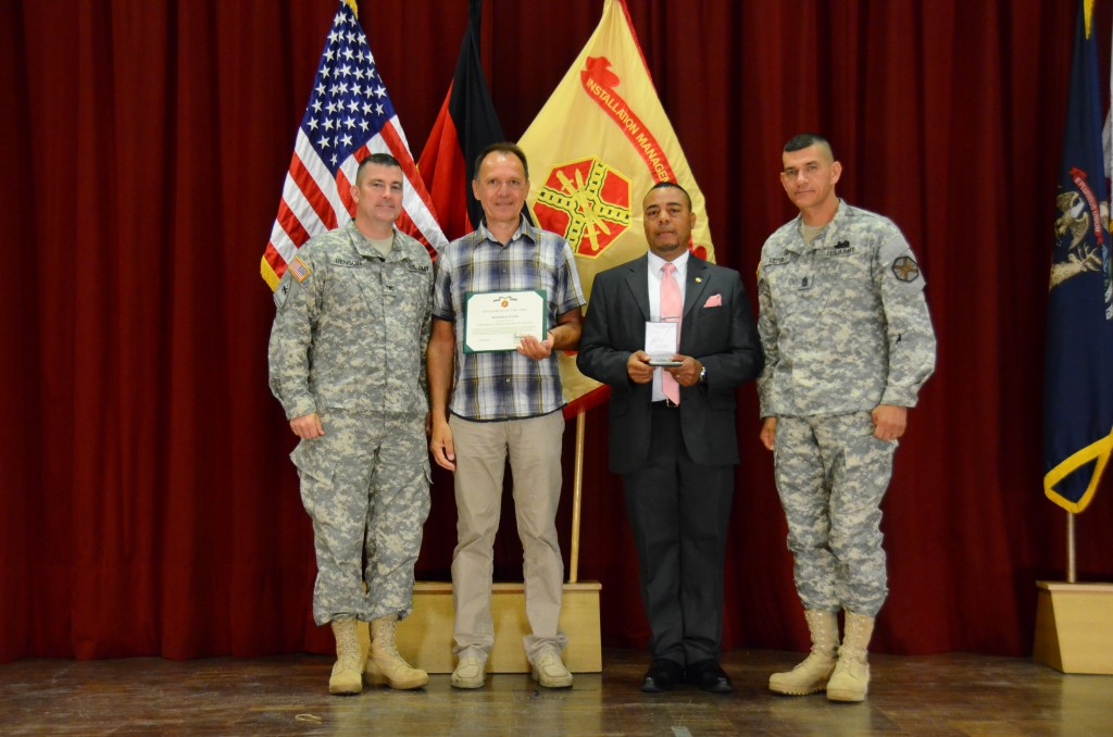 Reinhold Fuchs, second from left, a now-retired information technology specialist with U.S. Army Garrison Ansbach, receives a Commander's Award for Civilian Service during USAG Ansbach's All-Hands event and awards ceremony June 26 at Bismarck Theater. Fuchs stands alongside Col. Christopher M. Benson, left, USAG Ansbach commander; Mitchell L. Jones, second from right, USAG Ansbach deputy commander; and Command Sgt. Maj. Mark A. Kiefer, USAG Ansbach command sergeant major. Fuchs was one of six who received the award, in addition to nine members of Team Ansbach who received Certificates of Achievement and one more who received an Army Commendation Medal. The All-Hands gave USAG Ansbach employees an opportunity to give and receive feedback to the commander, and it gives the commander a chance to provide the workforce with a snapshot of the progress they have made as a team since the last All-Hands -- and a roadmap to the future. (U.S. Army photo by Stephen Baack, USAG Ansbach Public Affairs)