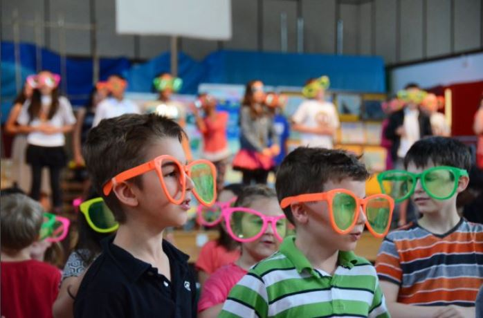 ILLESHEIM, Germany (June 4, 2015) -- Students of Illesheim Elementary School don oversized sunglasses as they participate in a song and dance medley during the school's closure and final awards ceremony in the gymnasium and auditorium June 4. The school closes after more than five decades of operation and after helping educate nearly 12,000 students. (U.S. Army photo by Stephen Baack, USAG Ansbach Public Affairs)