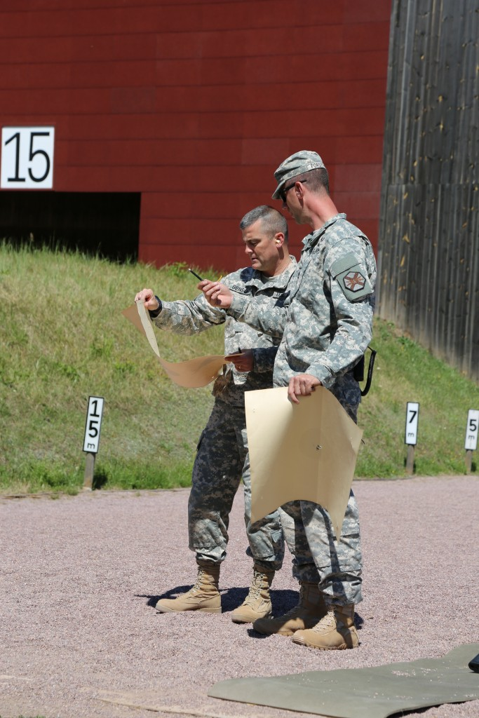 ANSBACH, Germany (July 14, 2015) -- Col. Christopher M. Benson, left, U.S. Army Garrison Ansbach commander, inspects his target with Sgt. 1st Class Robert Forsythe, right, equal employment adviser for USAG Ansbach. In collaboration with the town of Herrieden, Germany, U.S. Army Garrison Ansbach hosted an M16 rifle marksmanship competition at the garrison's Oberdachstetten Training Area July 10, 2015. The Herrieden Shoot, an annual event, is also known as the German-American Partnership Shoot and is an effort to promote positive community relations between USAG Ansbach and its local host nation partners. (U.S. Army photo by Bryan Gatchell, USAG Ansbach Public Affairs)