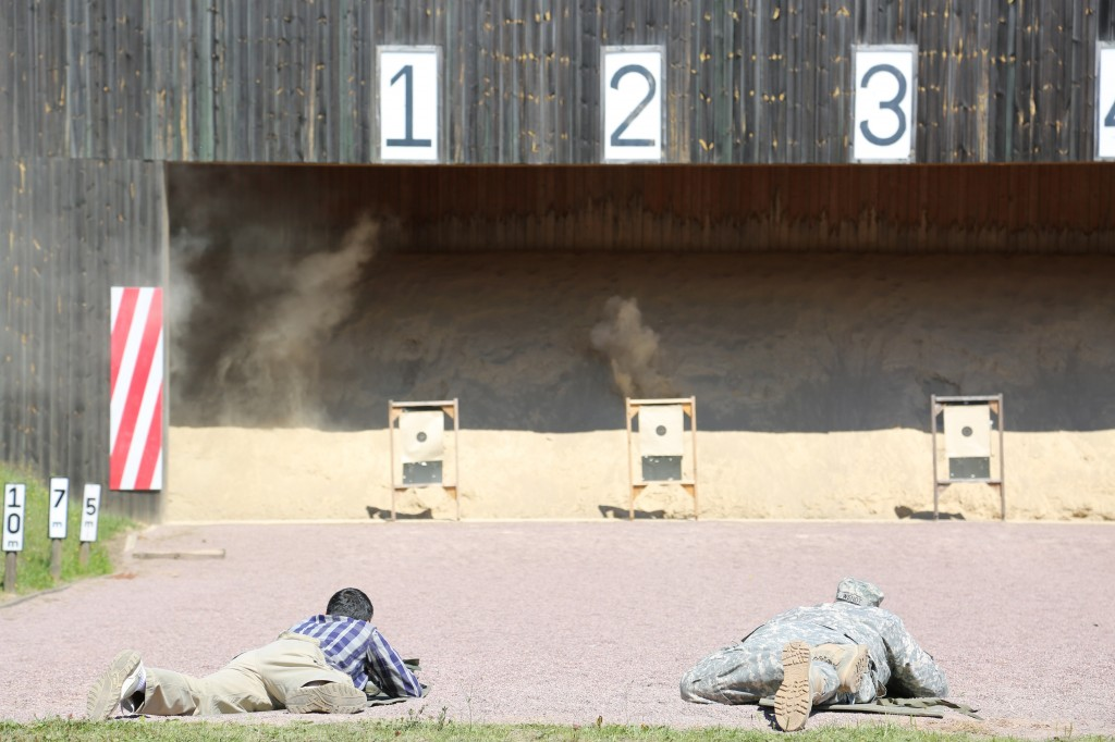 ANSBACH, Germany (July 14, 2015) -- Mardy Manning, left, U.S. Army Garrison Ansbach administrative assistant, and Master Sgt. Steven Wendt, first sergeant for Headquarters and Headquarters Detachment, USAG Ansbach, aim and fire at their targets. In collaboration with the town of Herrieden, Germany, U.S. Army Garrison Ansbach hosted an M16 rifle marksmanship competition at the garrison's Oberdachstetten Training Area July 10, 2015. The Herrieden Shoot, an annual event, is also known as the German-American Partnership Shoot and is an effort to promote positive community relations between USAG Ansbach and its local host nation partners. (U.S. Army photo by Bryan Gatchell, USAG Ansbach Public Affairs)