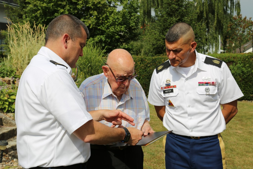 ANSBACH, Germany (July 21, 2015) – Col. Christopher M. Benson, left, U.S. Army Garrison Ansbach commander, and Command Sgt. Maj. Mark A. Kiefer, right, USAG Ansbach command sergeant major, present Eugene Green, World War II veteran and retiree, with a certificate of appreciation. Members of the USAG Ansbach command team visited Bamberg Friday to award a World War II veteran a certificate of appreciation signed by the U.S. president. (U.S. Army photo by Bryan Gatchell, USAG Ansbach Public Affairs)