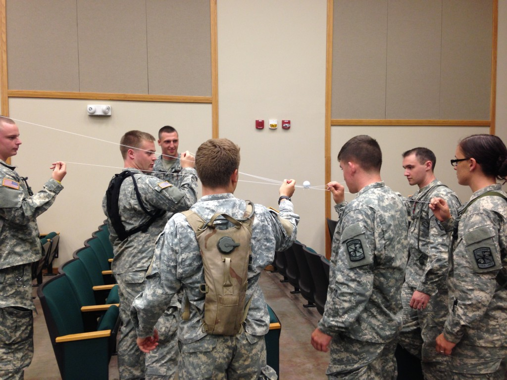 Cadets from 9th Regiment, Cadet Initial Entry Training, build confidence in themselves and their team by completing unfamiliar tasks, in this case, working together to keep a ping pong ball stabilized by pulling string taut, while moving it from point A to point B. (U.S. Army photo by Becky Farmer, Army News Service)