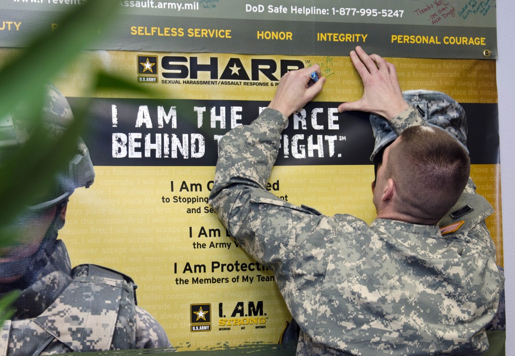 Sgt. Maj. of the Army Daniel Dailey signs the Sexual Harassment/Assault Response and Prevention poster hanging at the SHARP Resource Center during his visit to JBLM, March 2, 2015. Additionally, Dailey met with soldiers to talk about the future of the Army and what it takes to have a successful Army career. (U.S. Army photo by Sgt. Ryan Hallock, 19th Public Affairs Detachment)