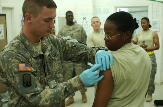 Spc. Joshua Ryan, a medic with the 16th Special Troops Battalion, 16th Sustainment Brigade, administers the influenza vaccine to Staff Sgt. Jacqueline Atkins at the troop medical clinic at Contingency Operating Base Q-West, Iraq. (U.S. Army photo)