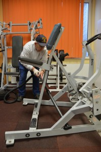 Kenneth Aungst, commander of the American Legion post, vacuums gym equipment.