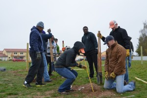 Members of the community dig a post hole for a dog park at Urlas Community.