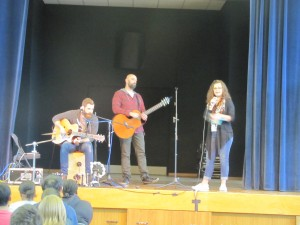 From left, Trevor Hager, Phil Stacey and a Club Beyond representative perform on stage. (Photo by Ajla Begic, Ansbach Middle High School Journalism)