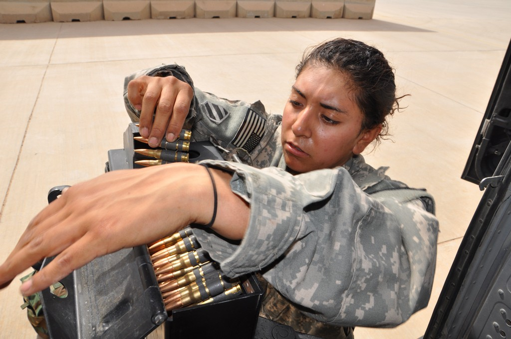 Spc. Crisma Albarran detaches an ammunition case from its mount after a UH-60 Black Hawk helicopter flight over Iraq, March 14, 2010. Albarran, with Task Force 38's B Company, 3rd Battalion, 158th Aviation Regiment, volunteered for the job as door gunner before her second deployment to Iraq, and has flown more than 100 hours toward her door gunner certification. During her first Iraqi deployment in 2007, she was a petroleum supply specialist with the 3rd Infantry Division. (U.S. Army photo)