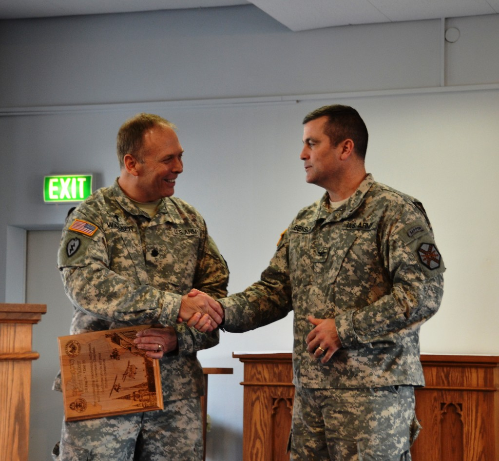 Col. Christopher M. Benson, right, U.S. Army Garrison Ansbach commander, presents Chaplain (Lt. Col.) R. Kent Walker with a token of the garrison's appreciation for service to the community during his time here as garrison chaplain. (U.S. Army photo by Bianca Sowders, USAG Ansbach Public Affairs)