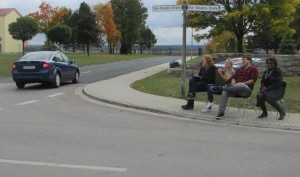 From left, Ansbach High School students Brooke Wendt, Liena Tatum, Tyler Wendt, and their street law teacher Linda Sykes sit near Rocket Park to observe driver behavior for a class project. (Photo courtesy of Serena Alfaro)
