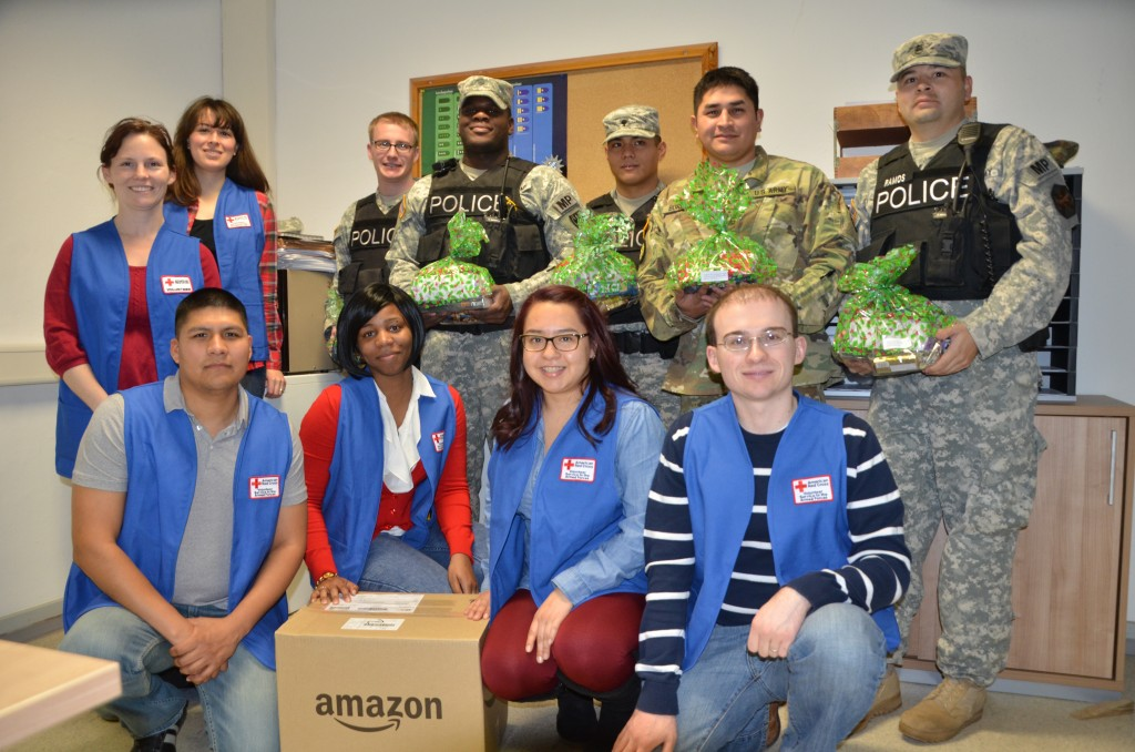 Volunteers with the U.S. Army Garrison Ansbach American Red Cross join military police Soldiers for a photo Dec. 25, shortly after the volunteers delivered gift boxes courtesy of Amazon. (Photo by Cassandra Wyatt, USAG Ansbach Red Cross Station Manager.)