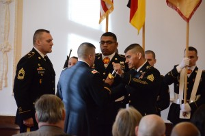 Command Sgt. Maj. Kiefer, center right, senior noncommissioned officer of U.S. Army Garrison Ansbach, passes the Sword of the Noncommissioned Officer to Col. Christopher M. Benson, USAG Ansbach commander, thus signifying Kiefer's relinquishment of responsibility as the garrison CSM.