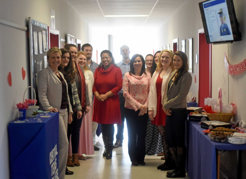 The staff of the Ansbach Education Center stand together amid Valentine's Day decorations and goodies before the Student Appreciation Day kickoff Feb. 10 at their Katterbach facility. (Photo by Stephen Baack, USAG Ansbach Public Affairs)