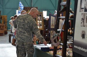 Sgt. Luke Park carries his daughter Laurel while he and daughter Lydia look at prices at the bazaar.