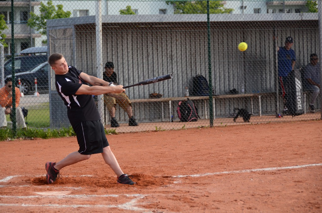 A Soldier from F Company, 5th Battalion, 158th Aviation Regiment, hits a line drive during a Ansbach's 2014 Unit Softball Championship held July 24 at Katterbach Army Airfield. (U.S. Army photo by Stephen Baack, USAG Ansbach Public Affairs).