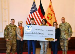 The volunteers of the year present the garrison commander, Col. Christopher M. Benson a symbolic check for hours donated by the community. (U.S. Army photo by Bianca Sowders)