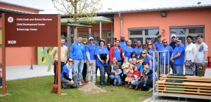 Ansbach community members stand together for a photo after burying a time capsule outside the Katterbach Child Development and School Age Center during the 30th anniversary celebration of the Month of the Military Child April 30, 2016. (U.S. Army photo by Stephen Baack, USAG Ansbach Public Affairs)
