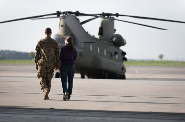 Sgt. Ryan Skinner, an AH-64 Apache Mechanic and his wife Marie Skinner, leave the hangar for a tour of a CH-47 Chinook helicopter prior to her flight aboard the aircraft.