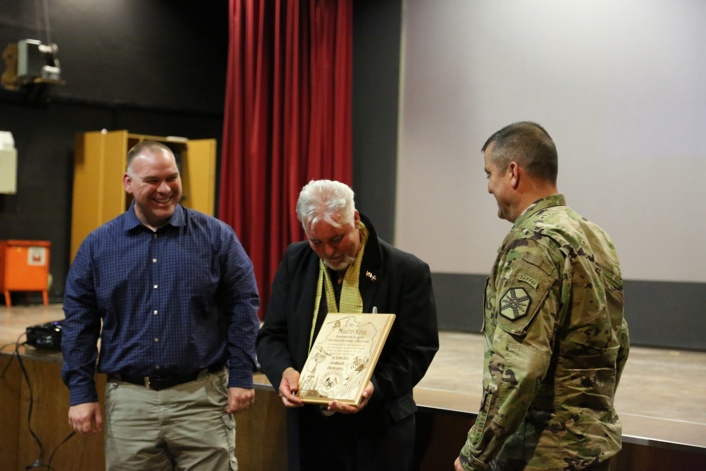 Historian and documentary film producer Martin King, center, receives a plaque from Chris Buchanan, left, Directorate of Plans, Training, Mobilization and Security, and from Col. Christopher M. Benson, right, U.S. Army Garrison Ansbach, following a screening of his film Searching for Augusta: The Forgotten Angel of Bastogne.