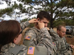 In this U.S. Army file photo, Stan Barney Capt. Jennifer Noetzel, chief of the Fort Drum Hearing Program, Preventive Medicine Department, fits an in-the ear TCAPS system for Pfc. Mark Epling, a member of 1st Battalion, 87th Infantry Regiment, 1st Brigade Combat Team, during hearing equipment testing at Fort Benning, Georgia, in December 2012. (Photo Credit: Stan Barney)