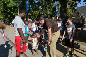 Col. Benjamin C. Jones, center right, U.S. Army Garrison Ansbach commander, congratulates a young 500-meter fun runner on his accomplishment.