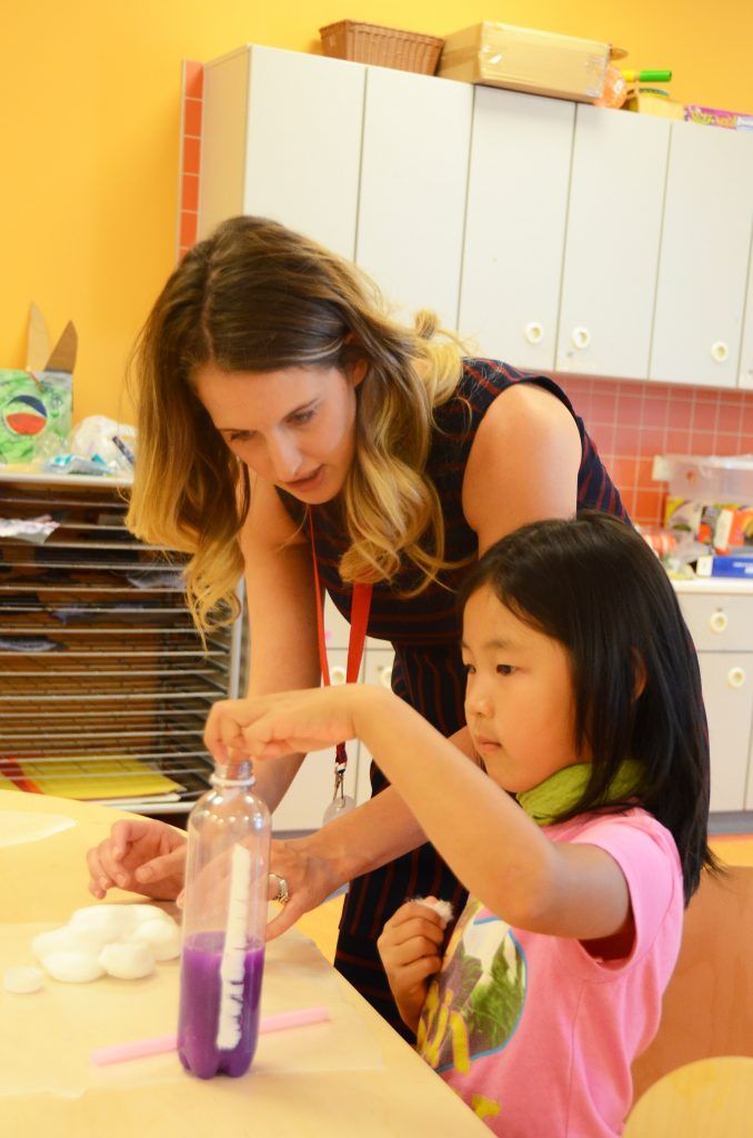 """Kayla Cook, left, a staff member at the Katterbach School Age Center, helps Ansbach Family member Claire An, who is spending part of her summer taking advantage of the offerings of Ansbach's Child, Youth and School Services, with a """"nebula jar"""" crafts project July 11, 2016, at Katterbach Kaserne, Germany. The project results in a fun object with the illusion that the gas and dust of deep space is inside an everyday container. (Photo by Stephen Baack, USAG Ansbach Public Affairs)"""