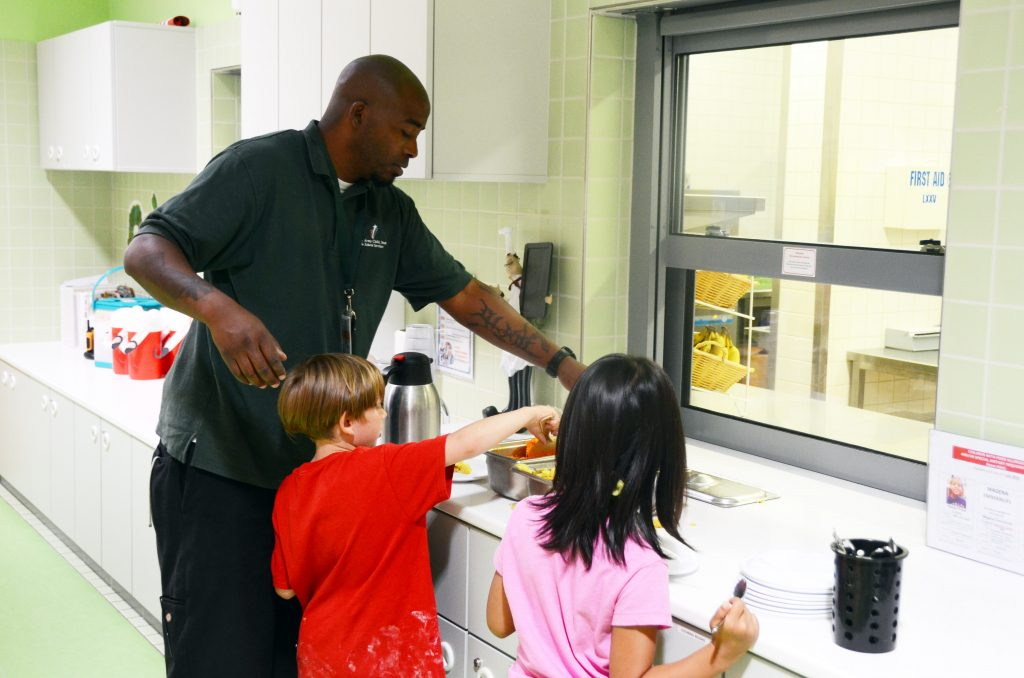 Will Smith, left, a staff member at the Katterbach School Age Center, gives a hand to Ansbach Family members Jonathan Haag, left, and Claire An, right, during lunchtime July 11, 2016, at Katterbach Kaserne, Germany. (Photo by Stephen Baack, USAG Ansbach Public Affairs)