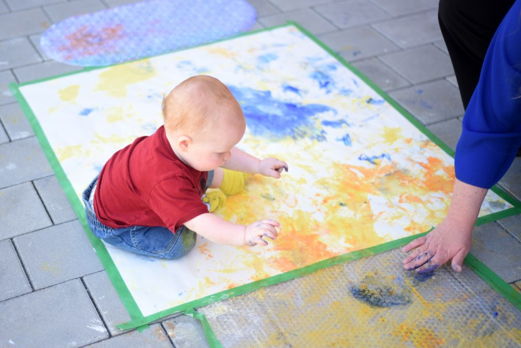 Ansbach Family member Killian Call creates a finger-painting masterpiece in the courtyard of the Katterbach Child Development Center July 11, 2016, at Katterbach Kaserne, Germany, while Pamela Storm, facility director, joins in on the fun. (Photo by Stephen Baack, USAG Ansbach Public Affairs)