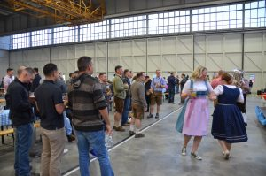Following a toast, a band from the German army plays and event organizers in Trachten dance.
