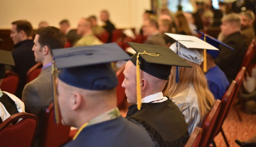 Graduates representing different colleges and universities sit together during the Nov. 16 Graduate Recognition Ceremony at the Von Steuben Community Center. The ceremony highlighted the achievements of 35 college graduates from among 18 institutions of higher learning.