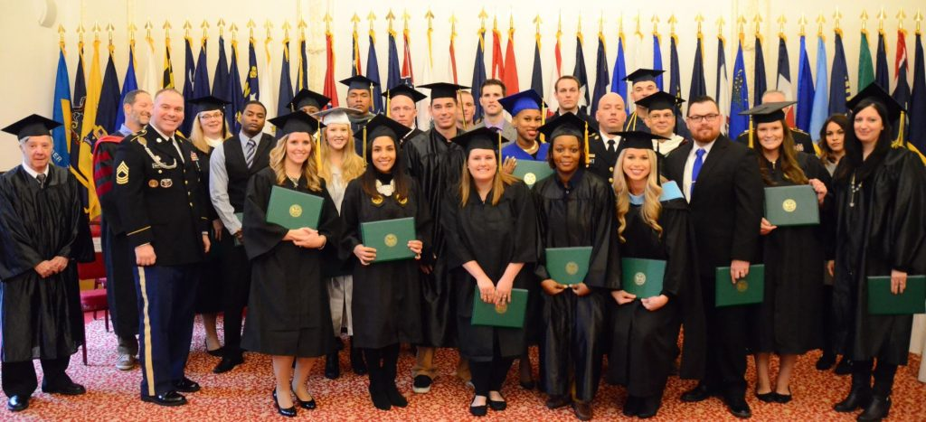 Graduates from around the U.S. Army Garrison Ansbach Education Center stand together for a photo after the Nov. 16 Graduate Recognition Ceremony at the Von Steuben Community Center. The ceremony highlighted the achievements of 35 college graduates from among 18 institutions of higher learning.