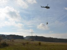 "A helicopter flies above Oberdachstetten Training Area to install ""bird diverters"" on high-tension power lines."