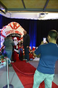 Aaron Michael Palencia, Ansbach's Better Opportunities for Single Soldiers president, takes a photo of the Atancio Family with Santa.