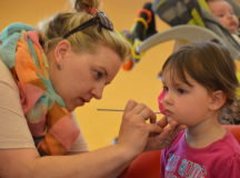 Nina Edmisten, member of the Parent Advisory Council, paints the face of Cora Hausauer during the Month of the Military Child kick-off event Thursday.