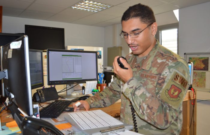 Senior Airman Christopher Ware, forecaster, Detachment 4, 7th Combat Weather Squadron, gives a weather brief over the radio to an aviator preparing for takeoff at Katterbach Army Airfield, Germany. Ware and eight other Airmen are attached to the 12th Combat Aviation Brigade providing decision-grade weather intelligence and combat-credible forces.